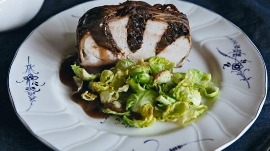Rôti de porc aux pruneaux enroulé de lard sur un lit de choux de Bruxelles